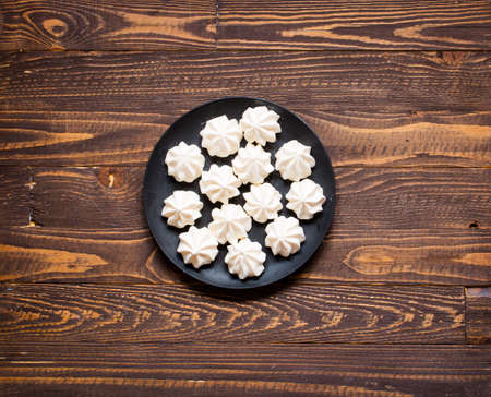 Sweet white meringue and other components on a wooden background, free space for text. Top view.