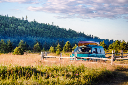 Vacation summer van trip with friends on sunset near mountains.