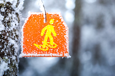 Snowshoeing hiking sign marker in trail snowy forest. Stock Photo