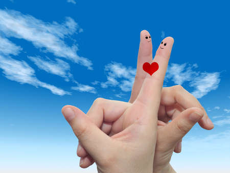 Conceptual fingers in love over blue sky with a heart painted photo