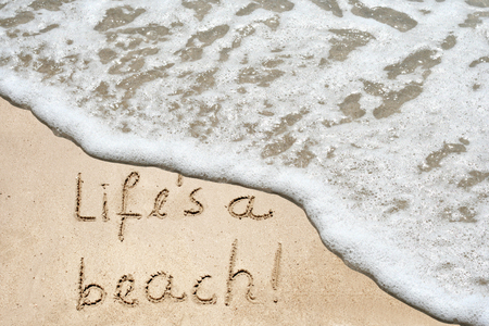 Conceptual life is a beach text in sand and water wave background photo
