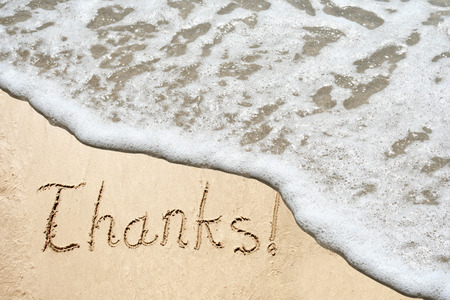 Conceptual thank you text in sand and water wave background photo