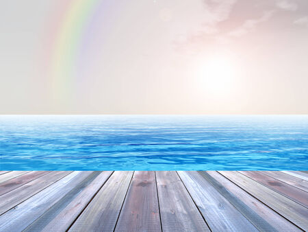 Concept or conceptual wood deck over blue sea and sky with rainbow photo