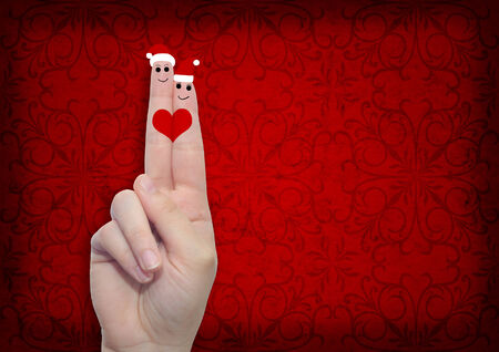 celebration party: Conceptual Christmas fingers in love on vintage old red background Stock Photo