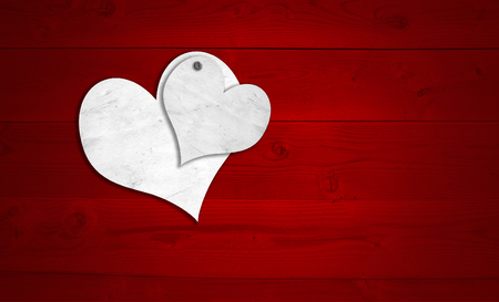 Concept or conceptual two white old paper vintage hearts nailed on red wood or wooden background for Valentine`s day photo