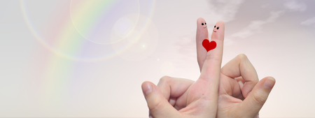 happy wedding: Conceptual fingers in love, with a painted heart shape over rainbow sky background banner