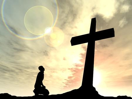 Conceptuele religie zwart kruis met een man bidden bij zonsondergang op de achtergrond