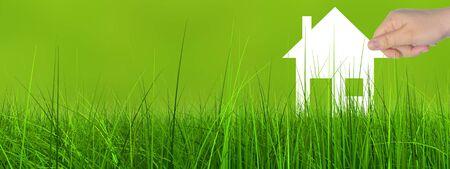 概念または概念のホワイト ペーパー家のシンボルは緑の夏草背景バナーで女性が手で開催されました。