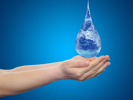 Conceptual blue water drop falling in hands on blue background