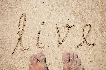 sandy feet: Conceptual hand drawn live text carved in a golden sandy beach with feet summer background