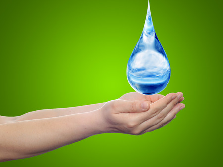 blue green background: Conceptual blue water drop falling in hands on green background