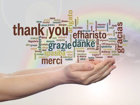 Conceptual thank you multilingual word cloud in hands on rainbow sky background
