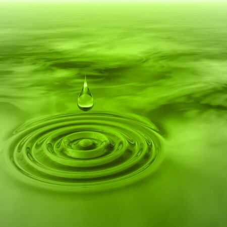 Conceptual green liquid drop falling in water with ripples and waves background Stock Photo