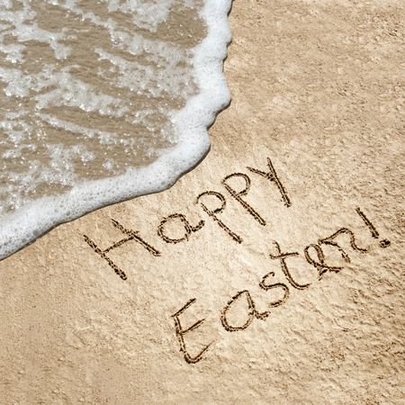 inscriptions: Concept or conceptual hand made or handwritten Happy Easter text in sand on a beach in an exotic island Stock Photo