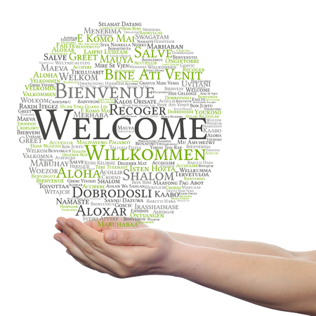 Concept or conceptual welcome or greeting international word cloud in hand, multilingual isolated Foto de archivo