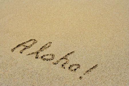 Aloha handwritten in sand on a beach as a mataphor for sun, summer, fun, holiday