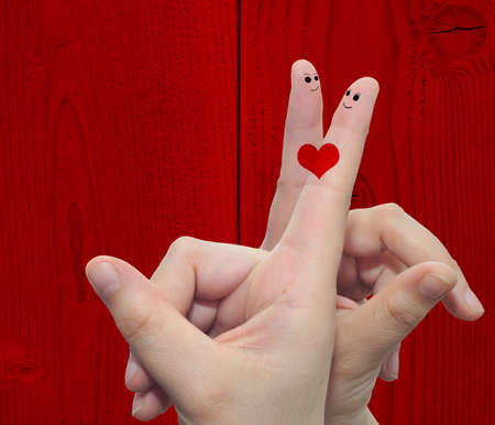Concept or conceptual human or female hands with two fingers painted with a red heart over a old vintage wood background for valentine, romantic, love, couple, young, family or wedding