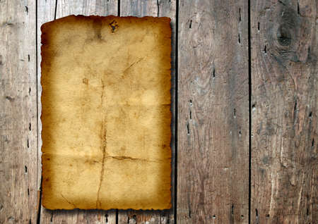 Vintage old grungy paper banner over ancient wood texture background metaphor for aged, retro, wooden, dirty, textured, manuscript, antique, parchment, book, ancient, weathered or grungy