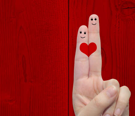 Concept or conceptual human or female hands with two fingers painted with a red heart over a old vintage wood background for valentine, romantic, love, couple, young, family or wedding Banco de Imagens - 155970110