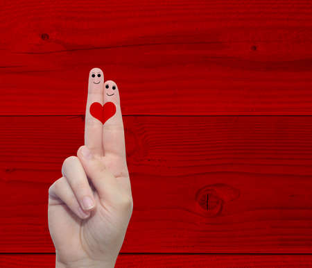 Concept or conceptual human or female hands with two fingers painted with a red heart over a old vintage wood background for valentine, romantic, love, couple, young, family or wedding Banco de Imagens - 155970120