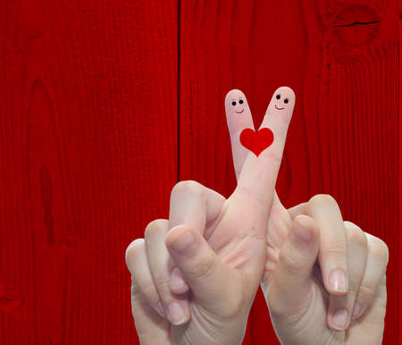Concept or conceptual human or female hands with two fingers painted with a red heart over a old vintage wood background for valentine, romantic, love, couple, young, family or wedding Banco de Imagens - 155960044