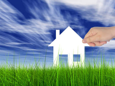 Concept or conceptual white paper house held in hand by a man in a green summer grass over a blue sky background with clouds, a symbol for construction, eco, ecology, loan, mortgage, property or home Banco de Imagens - 156191447