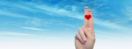 Concept conceptual human or female hands with two fingers painted with a red heart and smiley faces over cloud blue sky background for valentine, romantic, love, couple, young, family wedding