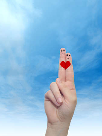 Concept or conceptual human or female hands with two fingers painted with a red heart and smiley faces over cloud blue sky background for valentine, romantic, love, couple, young, family or wedding Banco de Imagens - 156326302