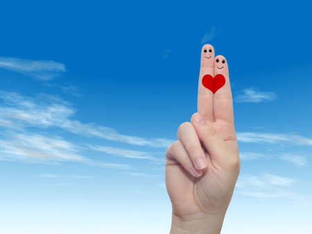Concept or conceptual human or female hands with two fingers painted with a red heart and smiley faces over cloud blue sky background for valentine, romantic, love, couple, young, family or wedding Banco de Imagens - 156326326