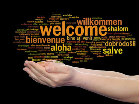Concept or conceptual abstract welcome or greeting international word cloud in hand, different languages or multilingual, metaphor to world, foreign, worldwide, travel, translate, vacation or tourism Banco de Imagens