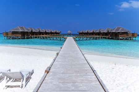 Beautiful tropical Maldives resort hotel with beach and blue water for relax. Maldives beach on cute island. White sand beach with a coral reef. Best beach for relaxation, sunbathing and snorkeling.
