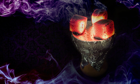 Hookah hot coals for smoking shisha and leisure in east pattern background. Hookah bowl with coal. Hookah wallpaper or best shisha art for web. Hookah craft strong tobacco.