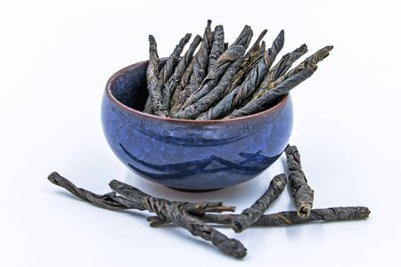 chinese holly: Kudin - Twisted Leaves of Ilex Latifolia Kudingcha. Bitter Chinese Green Tea in blue ceramic bowl isolated on white. Stock Photo