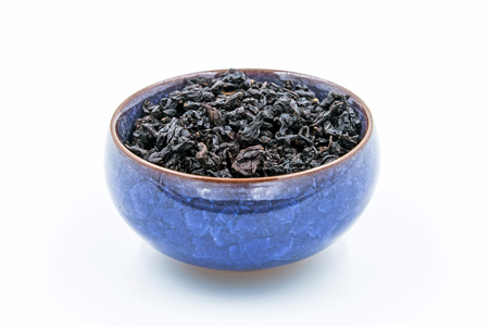 Chinese Oolong Dark Red tea (Black Tie Guan Yin) in a blue ceramic bowl isolated on white. Stock Photo