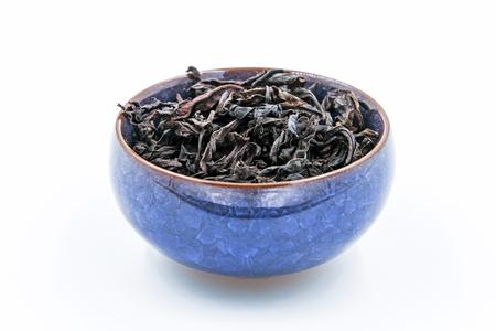 rou: Chinese Oolong Dark Red tea (WuYi Rou gui) in a blue ceramic bowl in a blue ceramic bowl isolated on white. Stock Photo