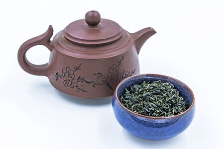 Chinese Wild Green tea. (Ye Sheng Lu Cha) in a blue ceramic bowl with small clay pot isolated on white.