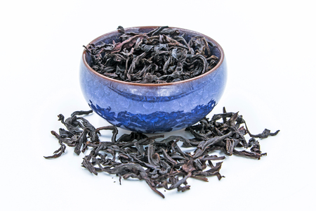 Chinese Oolong Dark Red tea (WuYi Rou gui) in a blue ceramic bowl isolated on white. Stock Photo