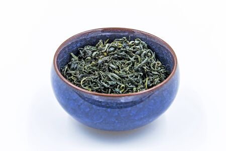 Chinese Wild Green tea. (Ye Sheng Lu Cha) in a blue ceramic bowl isolated on white.