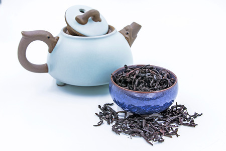 Chinese Oolong Dark Red tea (WuYi Rou gui) in a blue ceramic bowl in a blue ceramic bowl with small clay pot isolated on white. Stock Photo