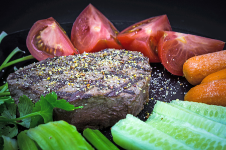 Delicious Chateaubriand beef steak on plate with vegetables, close-up