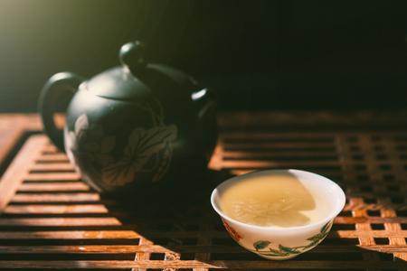 中国茶道。ティーポットと木製のテーブルに緑のプーアル茶のカップ。アジアの伝統文化