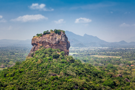 Spectacular view of the Sigiriya Lion rock surrounded by green rich vegetation. Picture taken from Pidurangala mountain in Dambula, Sri Lanka.