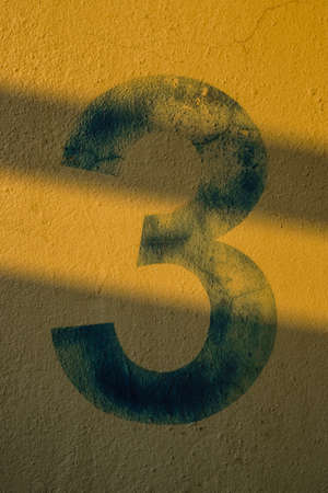 number 3: the number 3 on the wall under the shadow of the lights Stock Photo