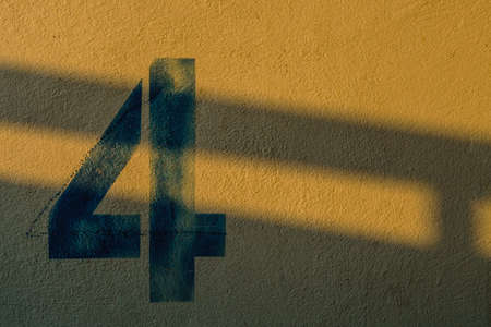 number 4: the number 4 on the wall under the shadow of the lights