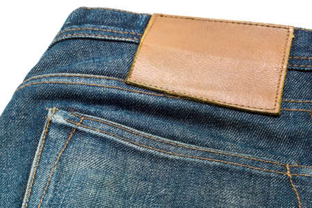 inner wear: Blank leather jeans label sewed on a blue jeans. Stock Photo