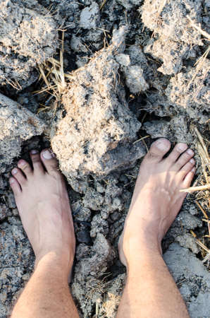 dirty feet: standing on dry and cracked ground,barren ground Stock Photo