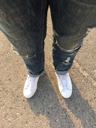 ripped jeans: Top view of male wearing ripped jeans and white shoes on cobbled road with sunset