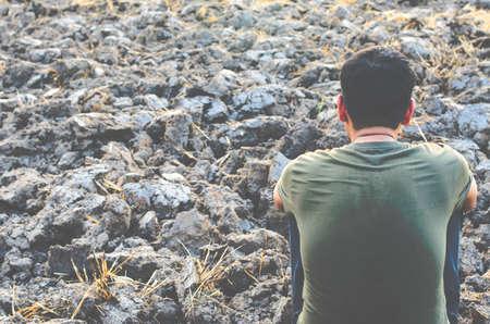 不毛の地面に座っている若い男が悲しい