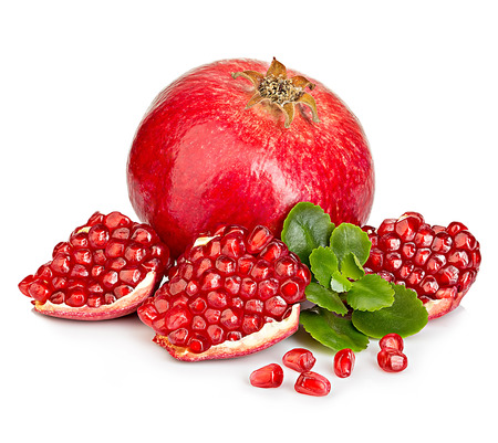 Ripe pomegranates with leaves close-up on a white background.