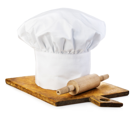 rollingpin: Original cooks cap with wooden rolling-pin on a wooden cutting board. Stock Photo